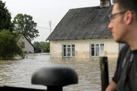 small_A man looks at houses half-submerged by flood water in the village of Swiniary