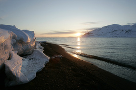 The sun shines low in the sky just after midnight over a frozen coastline near the Norwegian Arctic town of Longyearbyen, April 26, 2007. The sea water is normally frozen solid at this time of year but global warming may be warming the region.      REUTERS/Francois Lenoir   (NORWAY)