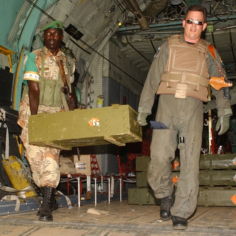 02 Oct 2005 - SSgt James Flaniken, a loadmaster with the 37th Airlift Squadron, Ramstein Air Base, Germany helps a Rwandan peacekeeper unload equipment from a U.S. Air Force C-130 Hercules aircraft deployed from Ramstein to the Sudan.  The C-130 is transporting Rwandan troops leaving the Sudan after six months of supporting the African Union mission in the Sudan.  U.S. Air Force photo by MSgt David D. Underwood, Jr. (Released)
