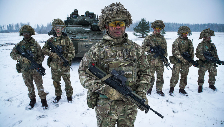 Corporal Lalabalavu from the Royal Welsh Regiment stands in front of his squad after exiting from a Warrior armoured fighting vehicle during an exercise near Tapa in Estonia. These troops form part of NATO's Enhanced Forward Presence battlegroup.
