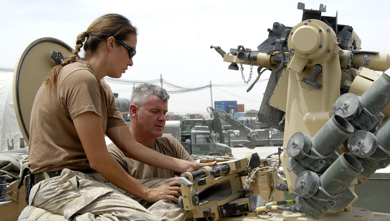 Kandahar Airfield, Afghanistan, 06 June 2007  Vehicle Maintenance section performs inspections  Canadian Forces technicians verify the function of a Remote Weapons System atop an RG 31 Armoured Personnel Vehicle at the Vehicle Maintenance section, Kandahar Airfield, Afghanistan. Weapons Technician Corporal Naomi Okimawininew (left) and Electronics/Optronics Technician Corporal Warren Westall, both from Deep River, Ontario, are currently serving with the Canadian Forces' Joint Task Force Afghanistan.  The Vehicle Maintenance section performs inspections, maintenance and repairs on trucks and armoured vehicles of all types used by the Canadian Forces in Afghanistan.  About 2500 members of the Canadian Forces (CF) are currently serving as part of Joint Task Force Afghanistan. Most of the soldiers are stationed at Kandahar Airfield and at Camp Nathan Smith, Canada's Provincial reconstruction Team (PRT) in Kandahar City. Other personnel are assigned to various military headquarters, a support base, and civilian organizations.  They play a key role in the NATO-led International Security Assistance Force mission whose goal is to improve the security situation in Afghanistan and assist in rebuilding the country.  Canadian Forces Image Number IS2007-7128 By MCpl Kevin Paul, Canadian Forces Combat Camera ____________________________________________Traduction  Aérodrome de Kandahar, Afghanistan, 6 juin 2007  La section de maintenance des véhicules procède à des inspections  Des techniciens des Forces canadiennes vérifient le fonctionnement d'un système de télécommande de tir dans la partie supérieure d'un véhicule blindé RG 31 à la section de maintenance des véhicules de l'aérodrome de Kandahar en Afghanistan. Le Caporal Naomi Okimawininew (à gauche), technicienne d'armement, et le Caporal Warren Westall, technicien en électronique/optoélectronique, les deux originaires de Deep River (Ontario), font actuellement partie de la Force opérationnelle int